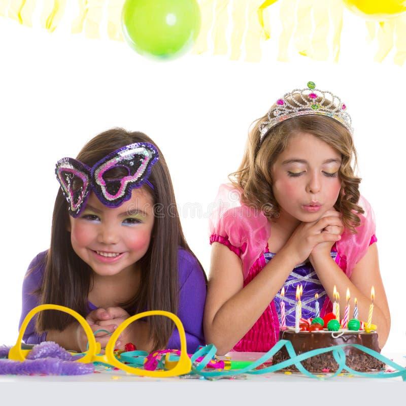 Muchachas felices de los niños que soplan la torta de la fiesta de cumpleaños imágenes de archivo libres de regalías