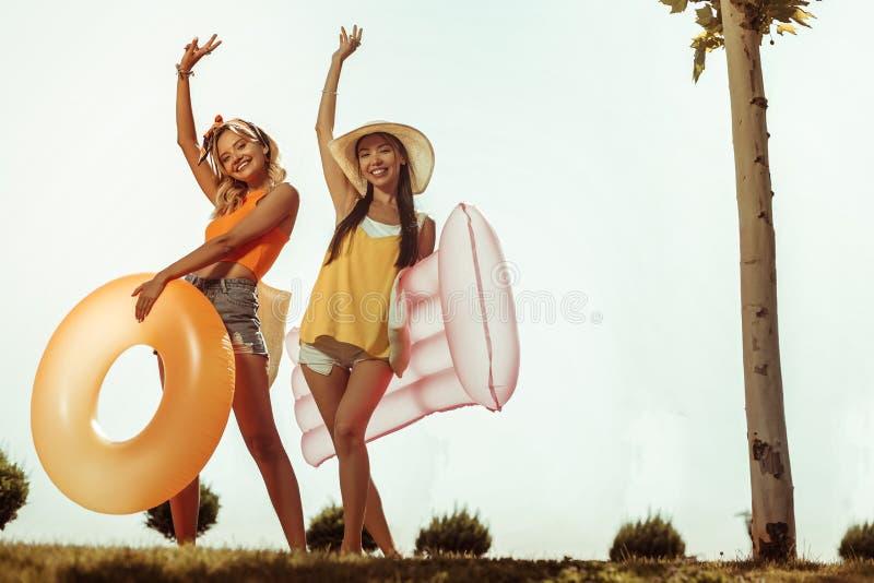 Muchachas felices del joven-adulto que presentan con la materia que nada al aire libre imagenes de archivo