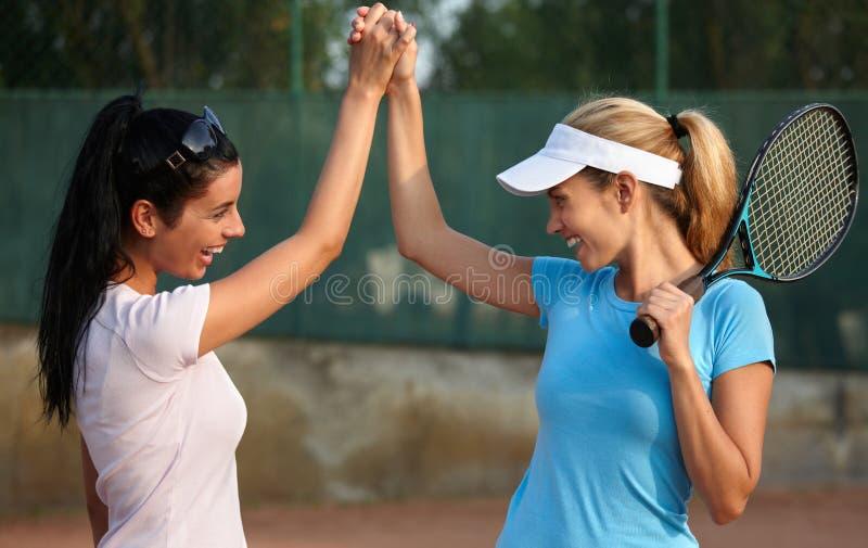 Muchachas felices en campo de tenis imagenes de archivo