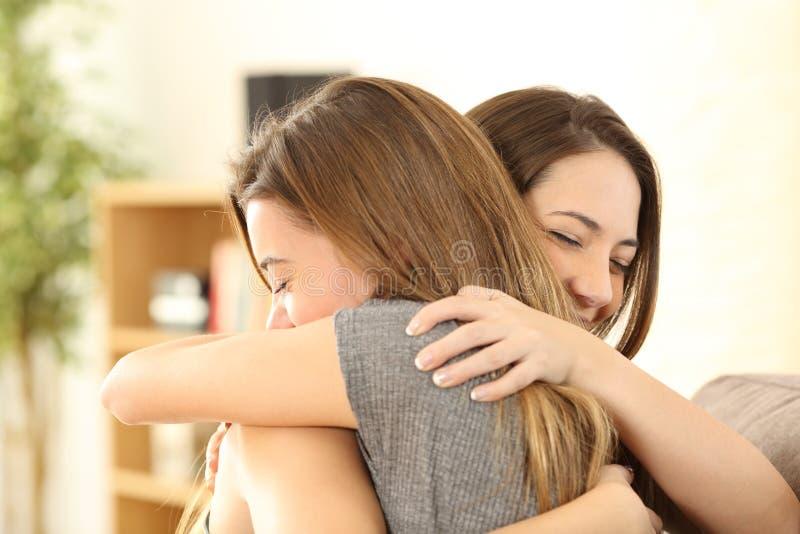 Muchachas felices que abrazan en casa imágenes de archivo libres de regalías