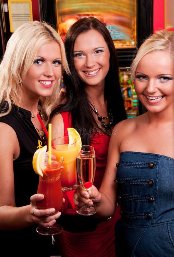 Muchachas felices que beben los cócteles imagenes de archivo