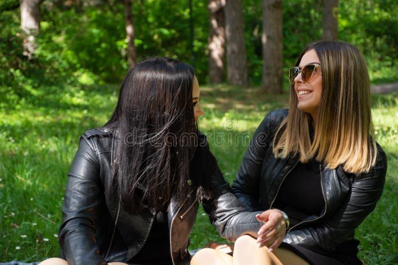 Muchachas felices que hablan en naturaleza y que se sientan en el prado, muchachas que sonríen y gozar en un día de primavera her imagenes de archivo