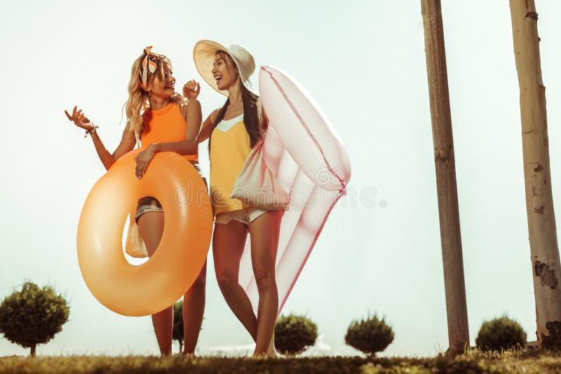 Muchachas felices que llevan la ropa de la playa que sostiene los juguetes inflables del agua imagenes de archivo