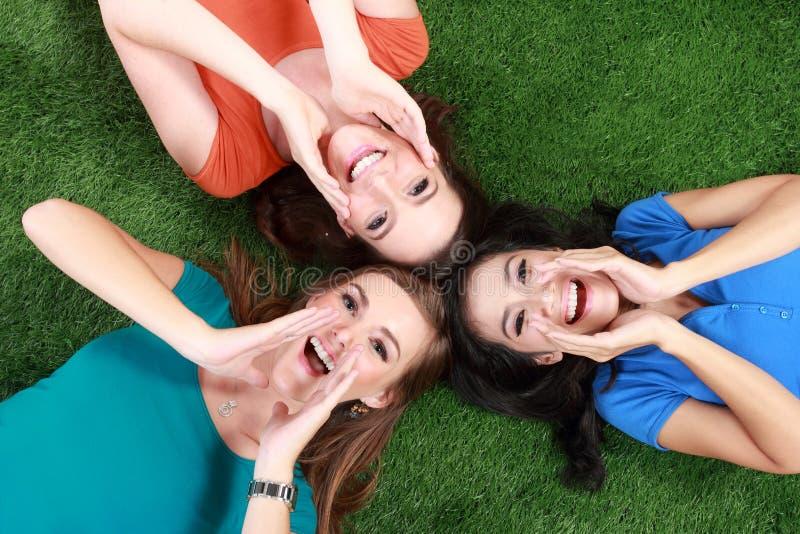 Muchachas felices que mienten en hierba verde imagenes de archivo