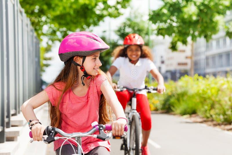 Muchachas felices que montan las bicis durante vacaciones de verano imagen de archivo