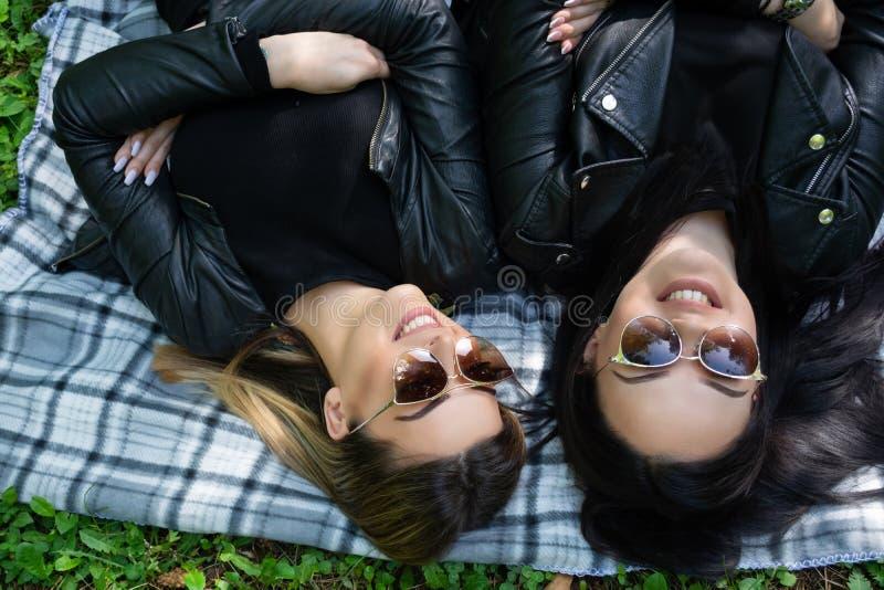Muchachas felices que se acuestan en la manta y la risa en un prado verde en un día de primavera en naturaleza fotografía de archivo