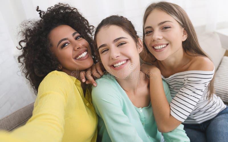 Muchachas felices que toman el selfie, divirtiéndose en casa imagenes de archivo