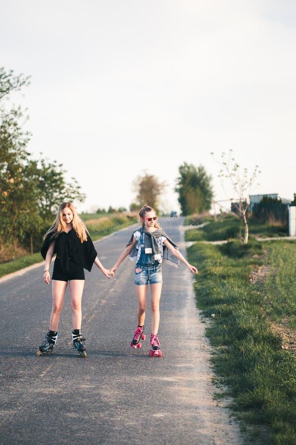 Muchachas felices sonrientes adolescentes que tienen rollerskating de la diversión, pasando el tiempo junto fotografía de archivo libre de regalías