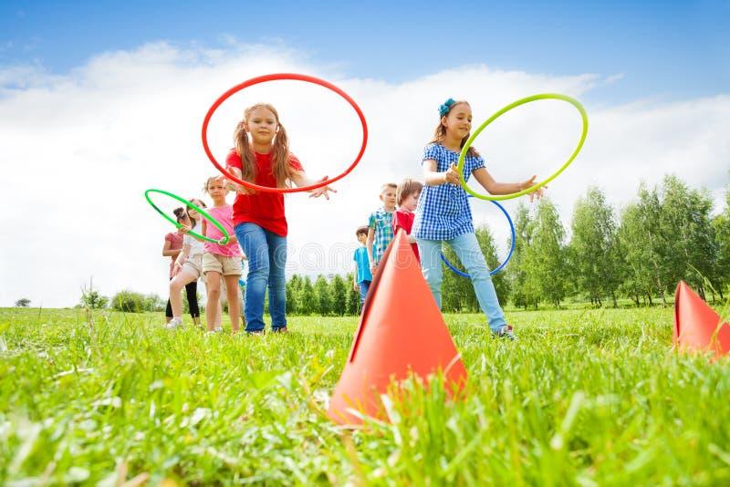 Muchachas felices y muchachos que lanzan aros coloridos imágenes de archivo libres de regalías