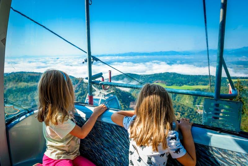 Muchachas gemelas que montan el teleférico de la cabina y que disfrutan de la visión foto de archivo