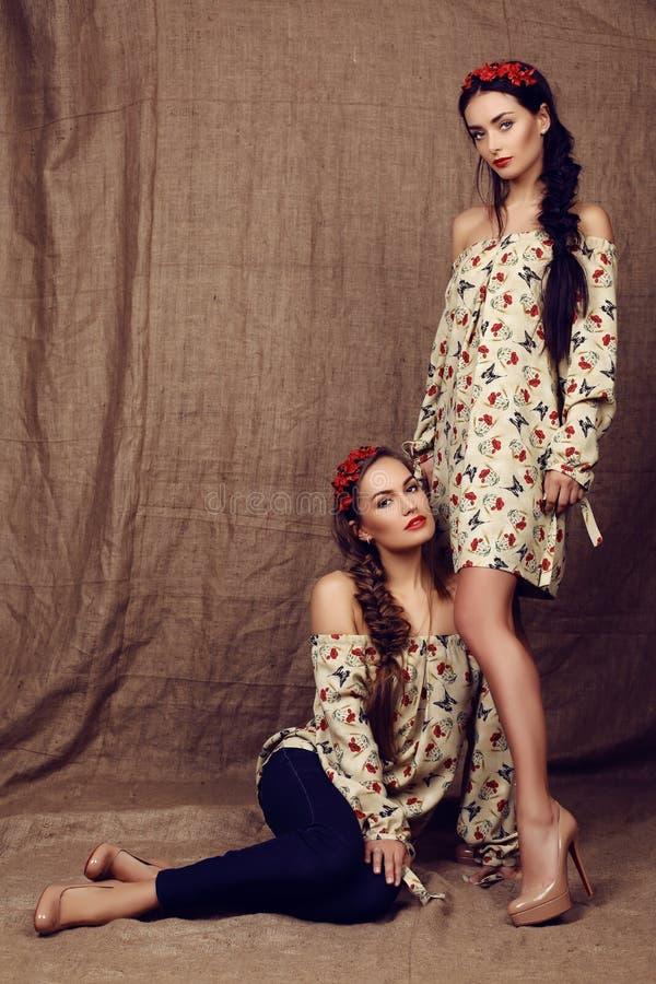 Muchachas hermosas con el pelo oscuro en vestidos con las impresiones de amapolas rojas fotos de archivo