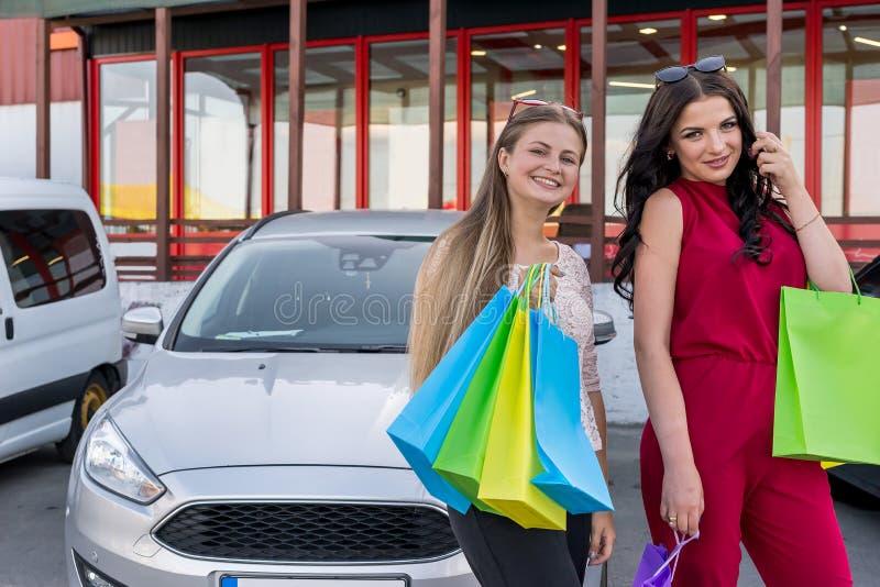Muchachas hermosas con los bolsos de compras en aparcamiento imagen de archivo