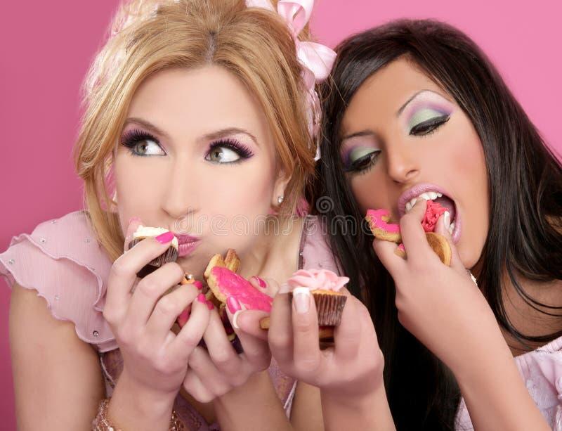 Muchachas hermosas de Barbie que comen el dulce de la dieta foto de archivo