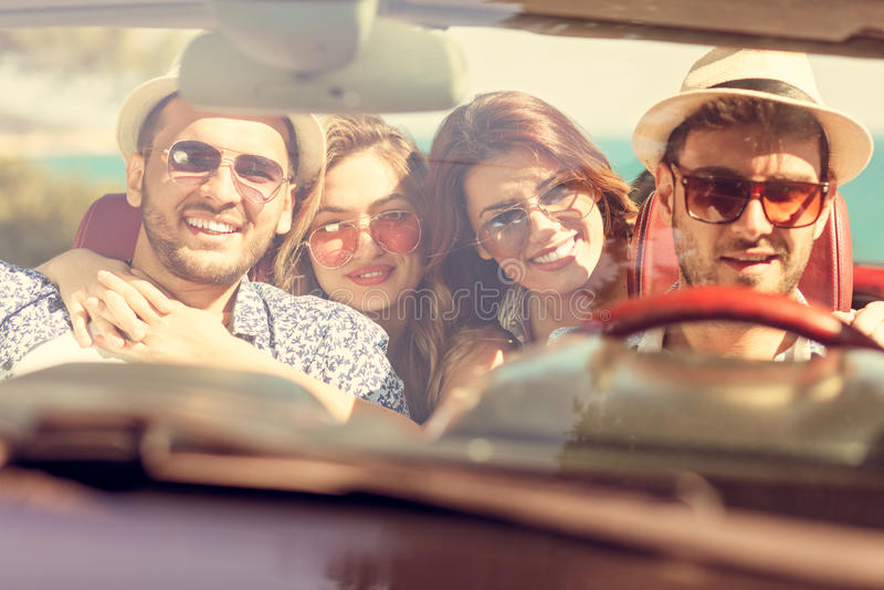 Muchachas hermosas del amigo del partido que bailan en un coche en la playa feliz imagen de archivo libre de regalías