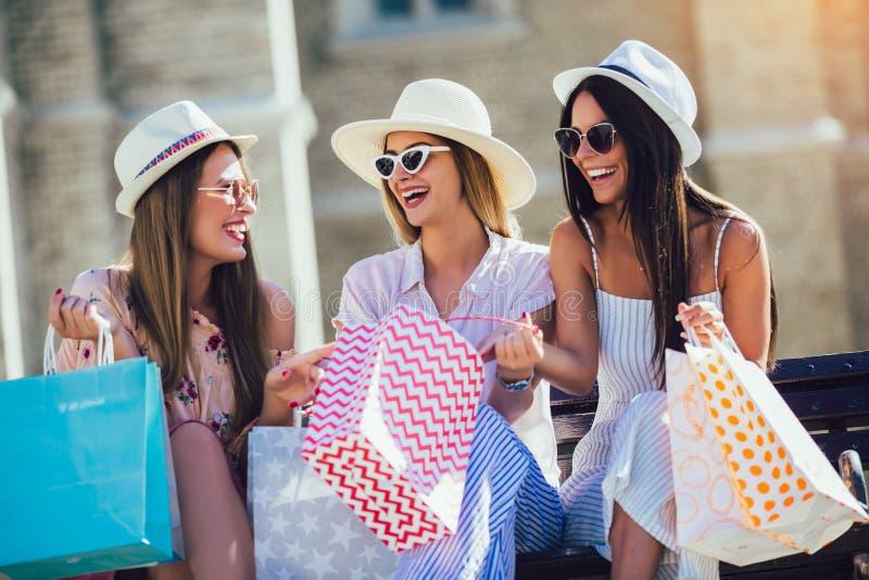 Muchachas hermosas en gafas de sol con los bolsos de compras en ciudad fotos de archivo libres de regalías