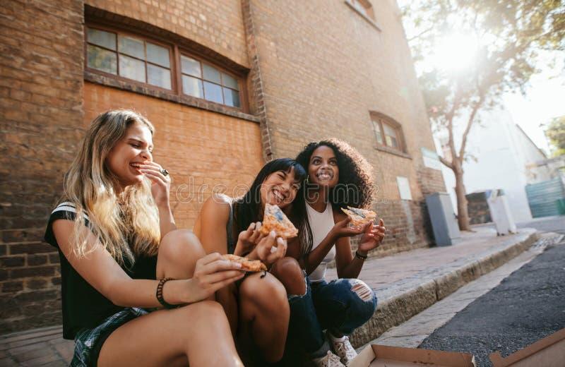 Muchachas hermosas que se sientan al aire libre por el camino que come la pizza fotos de archivo libres de regalías