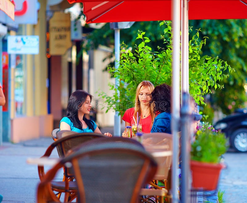 Muchachas hermosas que se sientan en la terraza del café, verano foto de archivo libre de regalías