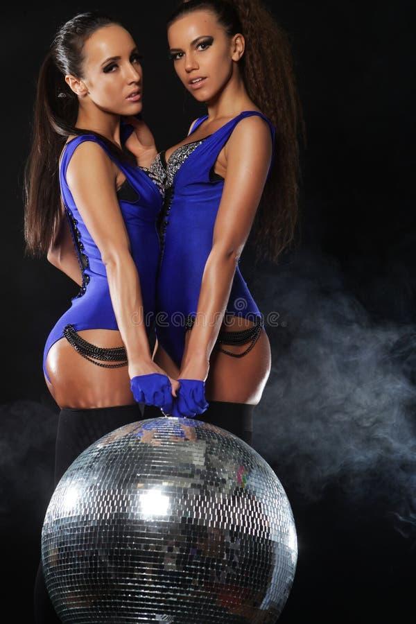 Muchachas jovenes del bailarín en humo con la bola de discoteca foto de archivo