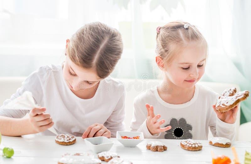 Muchachas lindas que adornan las galletas de Pascua imágenes de archivo libres de regalías