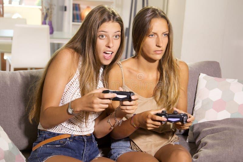 Muchachas lindas que juegan con los videojuegos en casa que se divierten foto de archivo libre de regalías