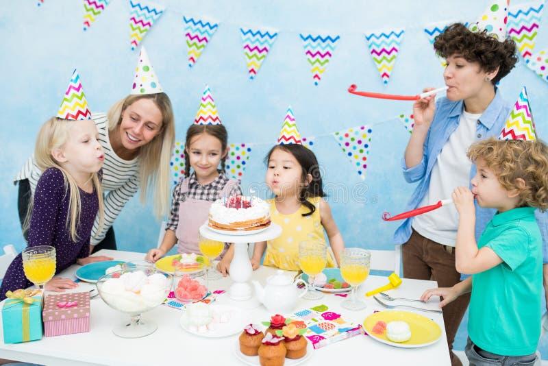Muchachas lindas que soplan hacia fuera velas en la torta imagen de archivo libre de regalías