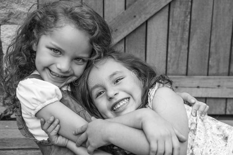 Muchachas morenas jovenes adorables que abrazan el abrazo fotografía de archivo libre de regalías