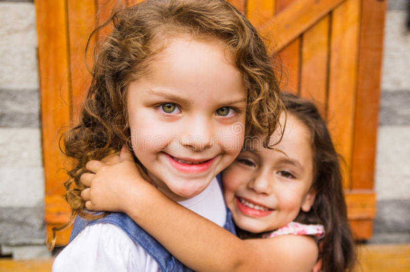 Muchachas morenas jovenes adorables que abrazan el abrazo foto de archivo