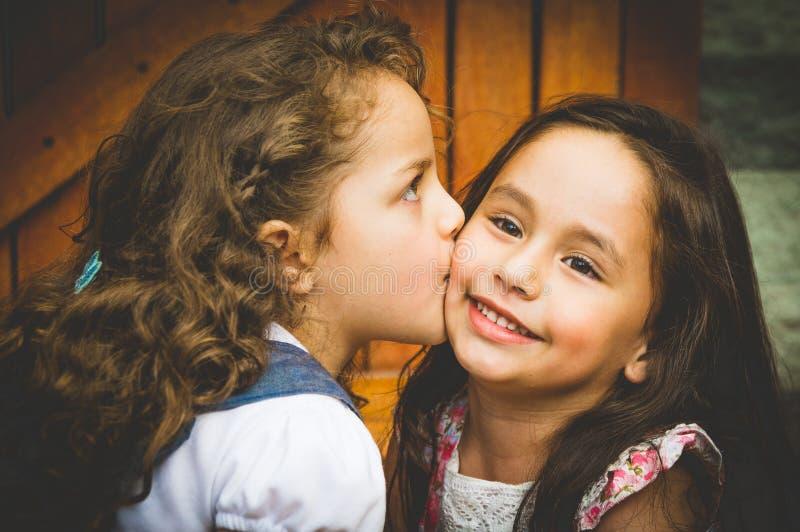 Muchachas morenas jovenes adorables que se besan en mejilla fotografía de archivo