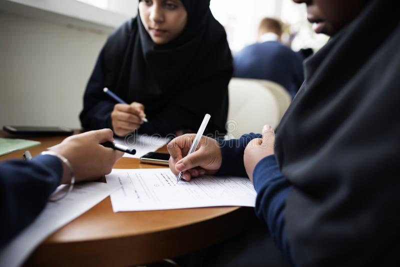 Muchachas musulmanes diversas que estudian en una sala de clase fotos de archivo libres de regalías