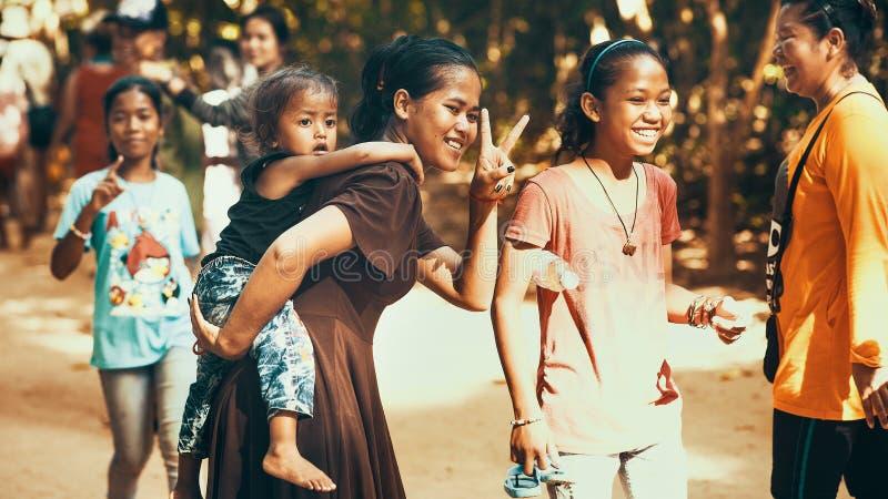 Muchachas no identificadas con los niños de la sonrisa camboyana imagen de archivo