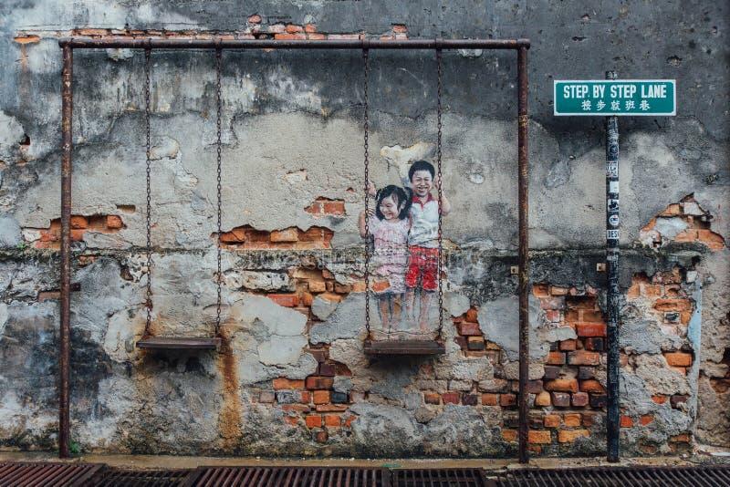 Muchachas pintadas que juegan el oscilación junto en el ladrillo viejo con el muro de cemento de la calle de George Town Penang,  fotografía de archivo