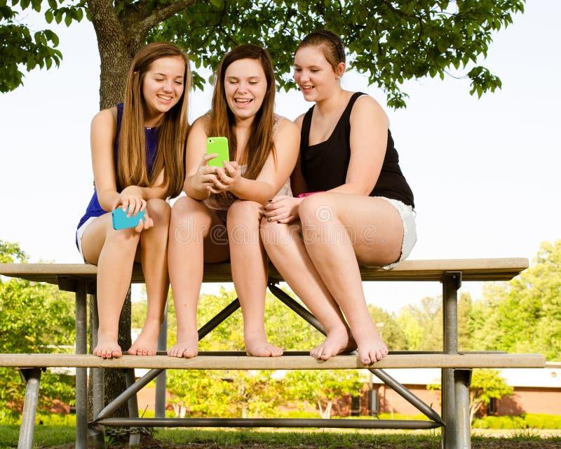 muchachas Pre-adolescentes que mandan un SMS mientras que cuelga hacia fuera en frente  fotos de archivo