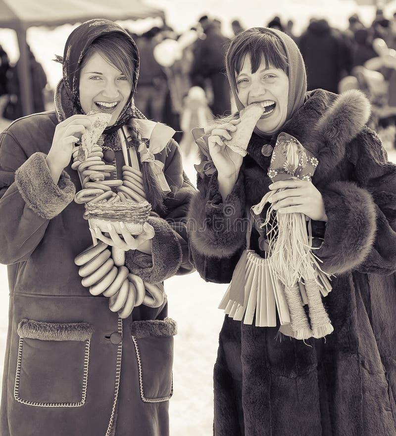 Muchachas que comen la crepe durante Shrovetide imagen de archivo libre de regalías