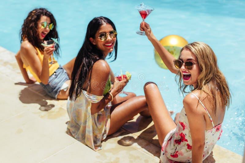 Muchachas que cuelgan hacia fuera por la piscina con las bebidas fotos de archivo