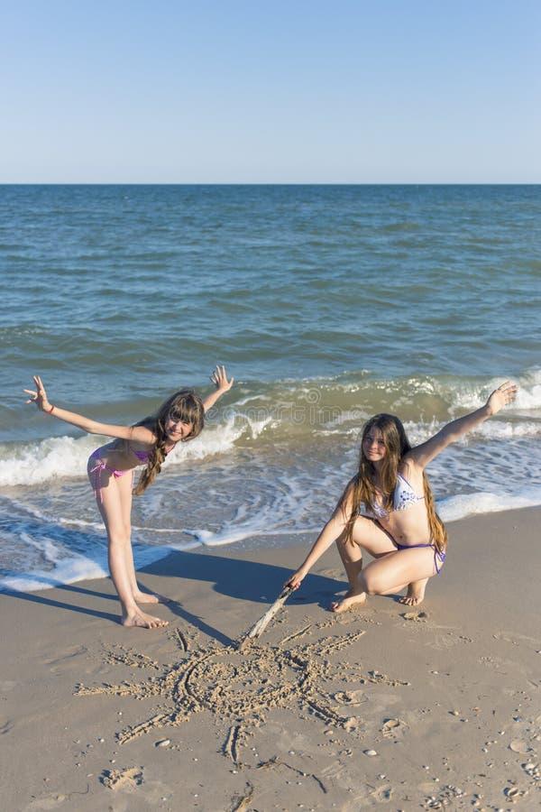 Muchachas que dibujan en la arena en la playa en el sol del verano foto de archivo libre de regalías