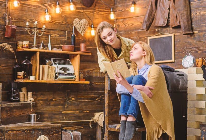 Muchachas que discuten el libro interesante Mamá e hija que leen la novela clásica Mujer que le enseña a la literatura adolescent imagen de archivo