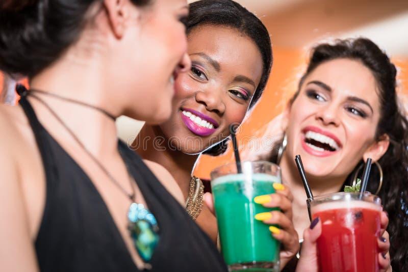 Muchachas que disfrutan de la vida nocturna en un club, cócteles de consumición imagen de archivo