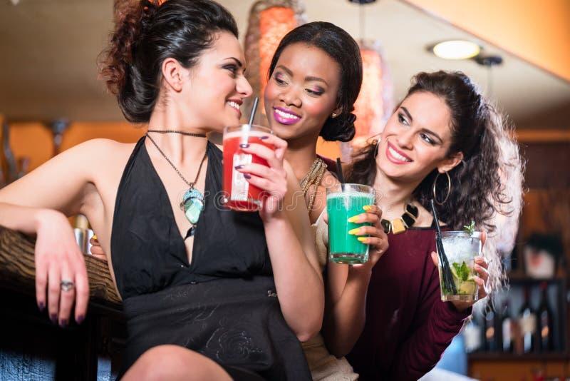 Muchachas que disfrutan de la vida nocturna en un club, cócteles de consumición imagenes de archivo