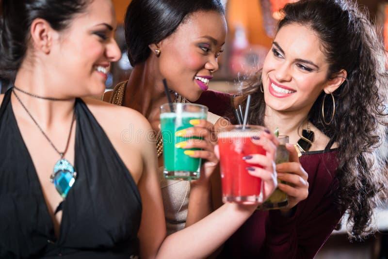 Muchachas que disfrutan de la vida nocturna en un club, cócteles de consumición foto de archivo