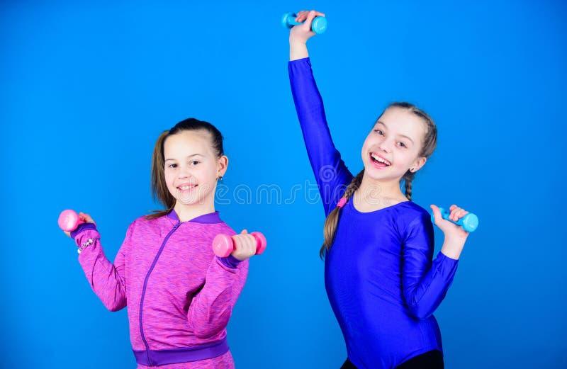 Muchachas que ejercitan con pesas de gimnasia Ejercicios de las pesas de gimnasia del principiante Los ni?os llevan a cabo el fon fotografía de archivo