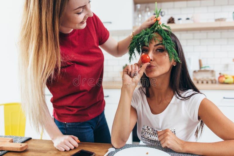 Muchachas que enga?an alrededor en la cocina que juega con las verduras foto de archivo