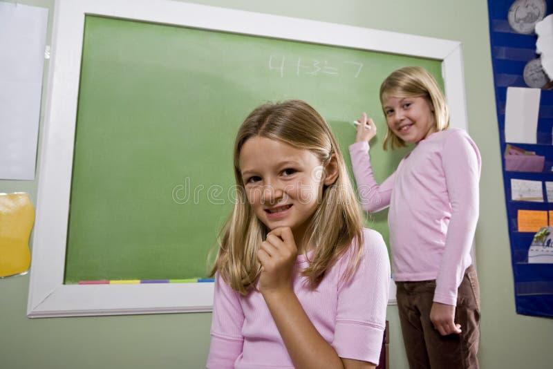 Muchachas que escriben en la pizarra en sala de clase imagenes de archivo