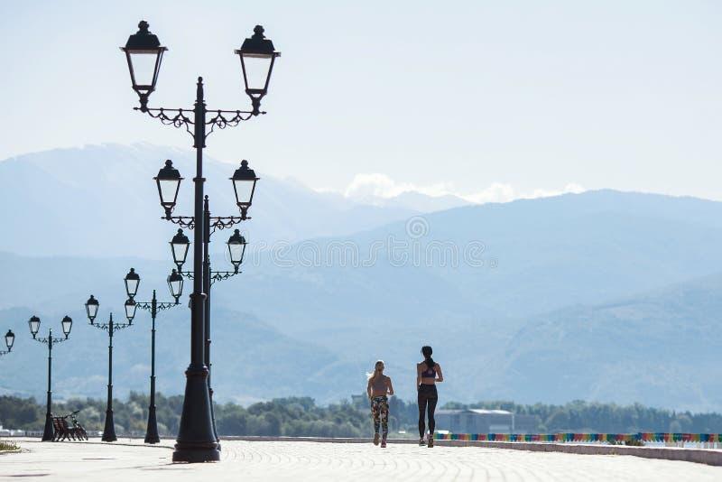 Muchachas que hacen los deportes, corriendo por la mañana a lo largo de la 'promenade' fotos de archivo