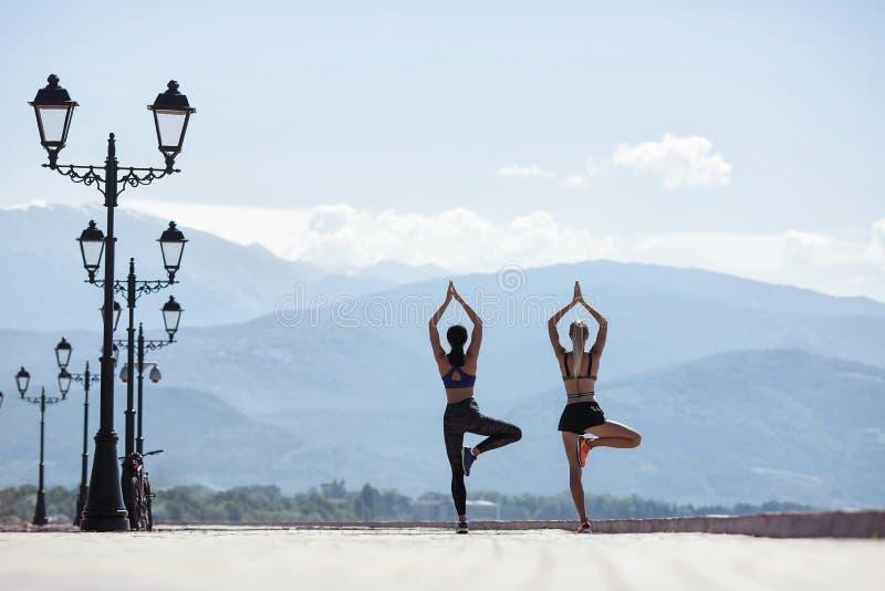 Muchachas que hacen yoga por la mañana, en la costa por el mar imagen de archivo