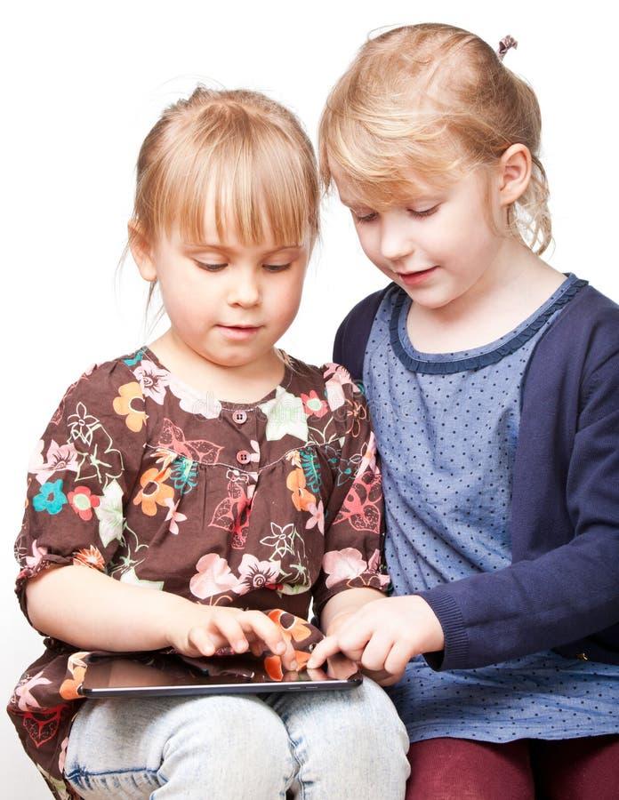 Muchachas que juegan con un ordenador de la tableta imagen de archivo