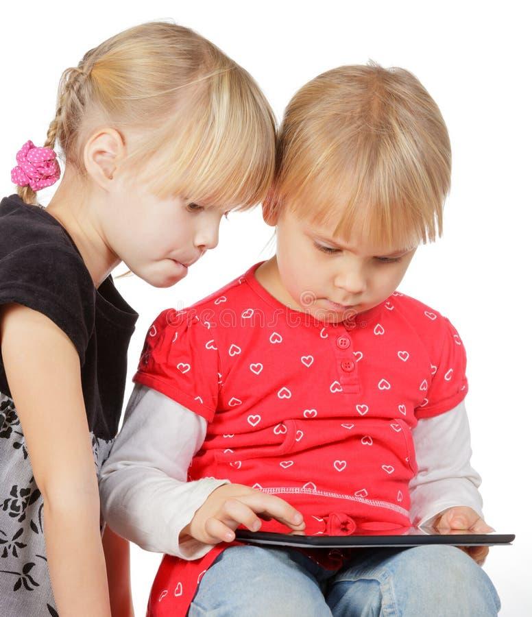 Muchachas que juegan con un ordenador de la tablilla fotografía de archivo