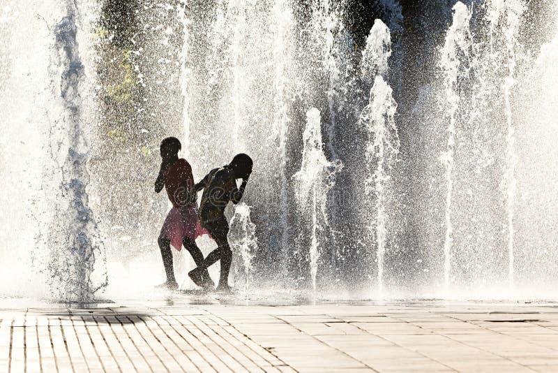 Muchachas que juegan en jets de agua imagenes de archivo