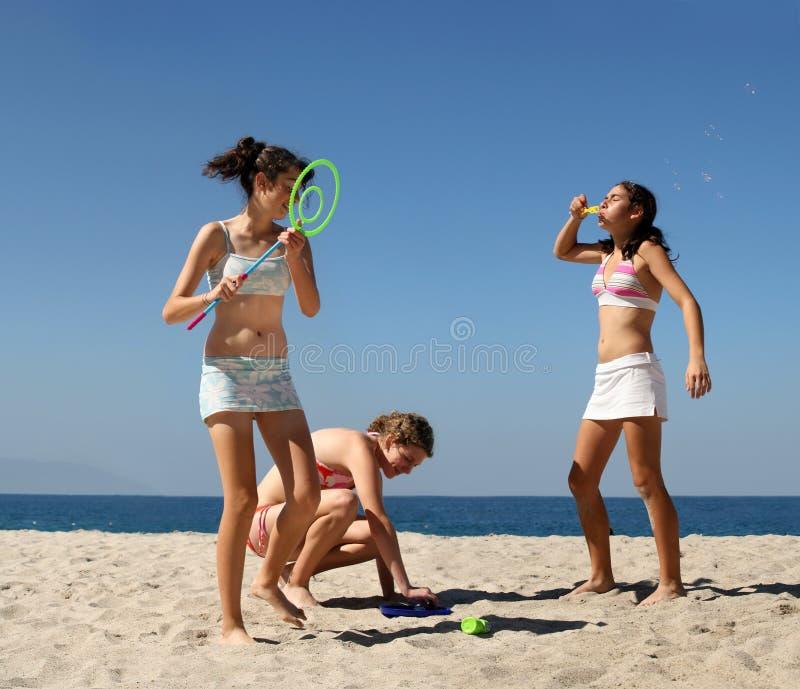Muchachas que juegan en la playa imagenes de archivo