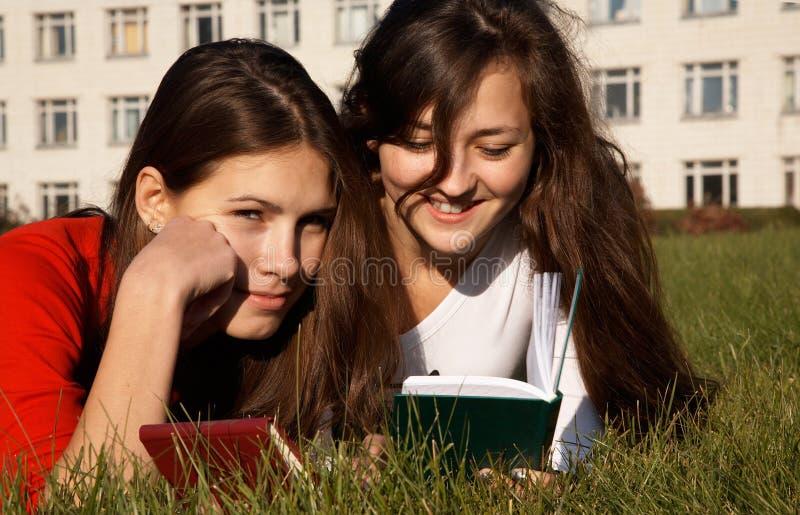 Muchachas que leen los libros en el césped imagen de archivo libre de regalías