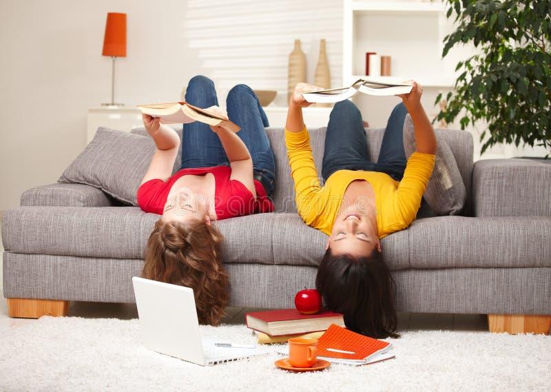 Muchachas que leen upside-down en el sofá imagenes de archivo